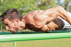 young-athlete-working-out-outdoor-gym-street-workout-exercises-tense-muscles-78612470[1]